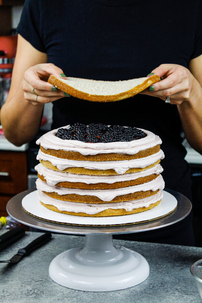 image of a blackberry layer cake being assembled with cinnamon cake layers, blackberry jam, fresh blackberries, and blackberry peach buttercream