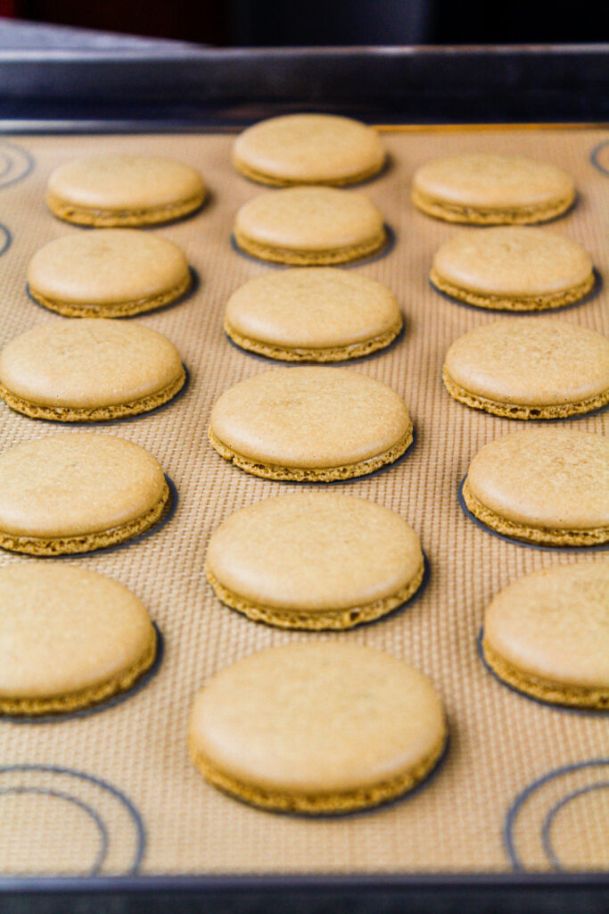 image of coffee flavored french macaron shells that have been baked and are cooling on. silpat mat