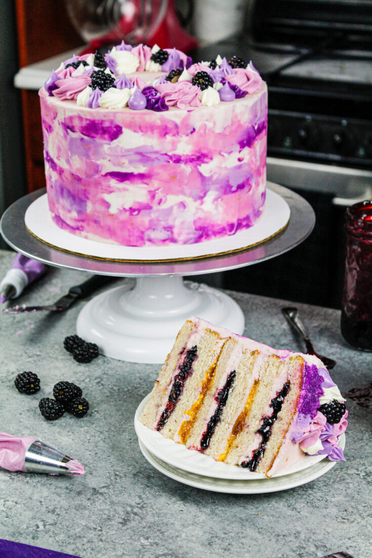 image of a beautiful blackberry and peach layer cake that's been cut into to show it's peach and blackberry filling