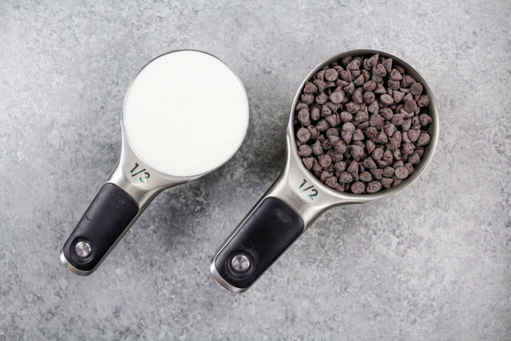 image of chocolate chips and heavy cream laid out on a counter to make a chocolate ganache drip for a chocolate cake