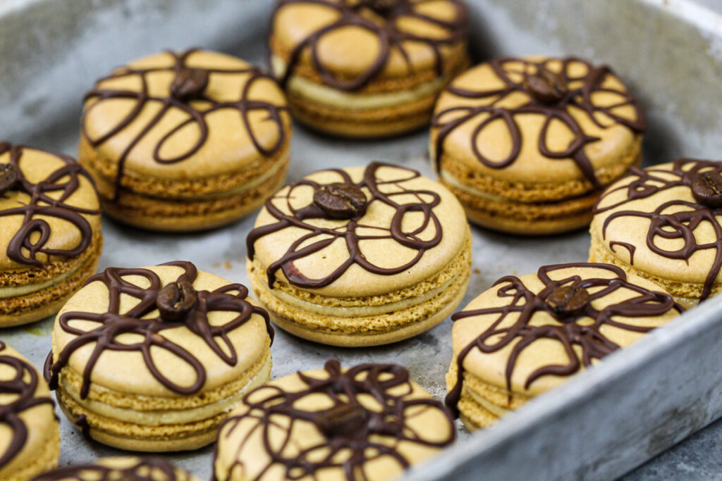 image of coffee macarons filled with coffee buttercream and decorated with a drizzle of dark chocolate and a coffee bean