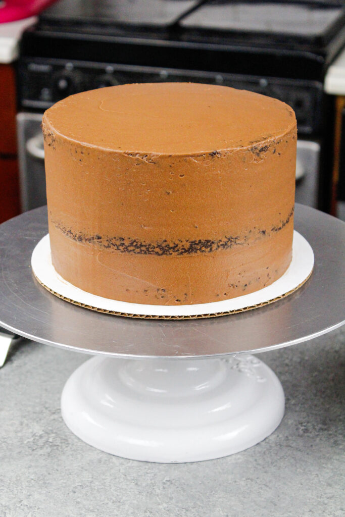 image of a chocolate cake that's been crumb coated and chilled and is ready for its second layer of chocolate buttercream frosting
