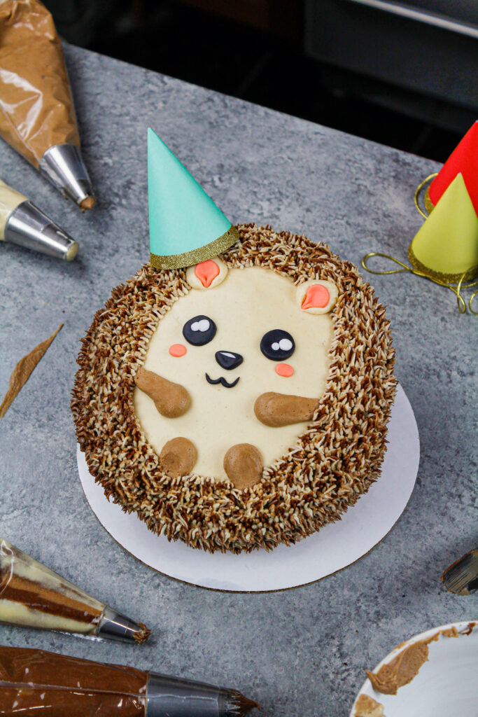 image of an adorable and easy to make hedgehog cake made with chocolate cake layers and buttercream frosting