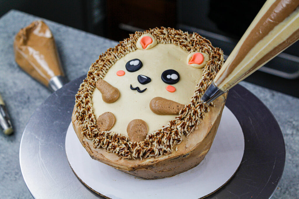 image of a buttercream hedgehog cake being piped with buttercream to look like quills