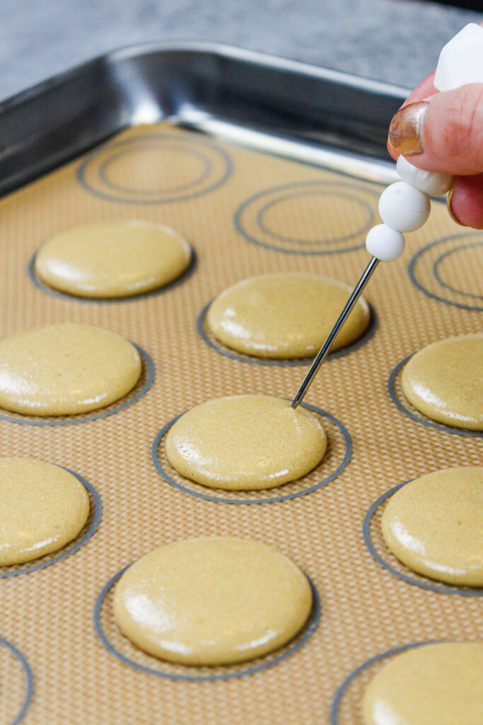 image of coffee macaron shells that have been piped and banged on a counter to release any air bubbles, which are being popped with a scribe