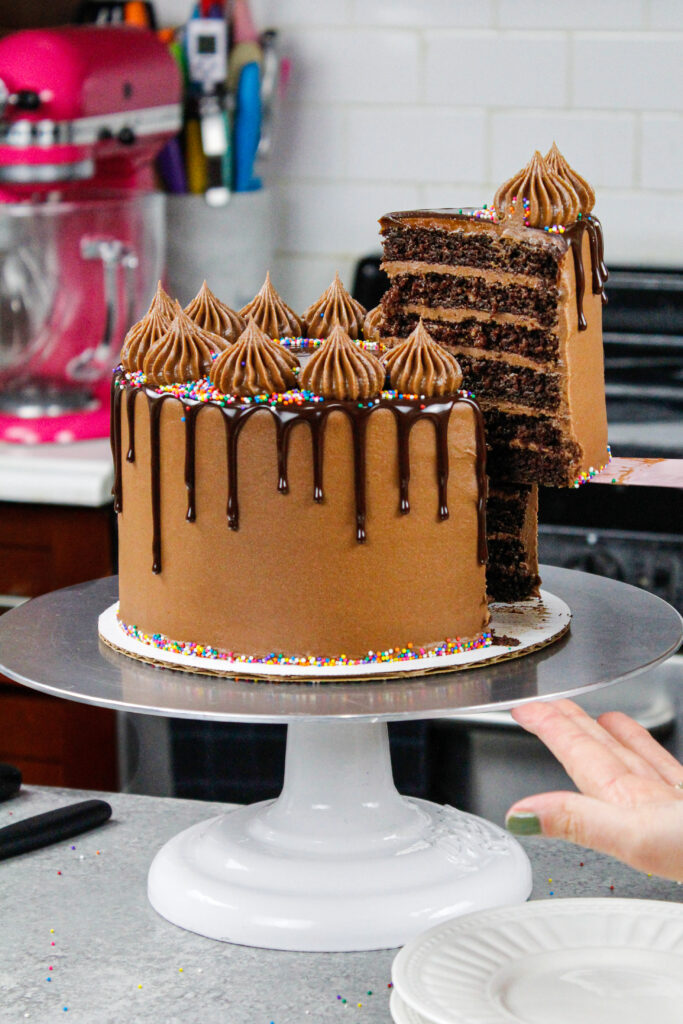 image of a chocolate drip cake that's been cut into and is having a slice pulled out to show it's six layers