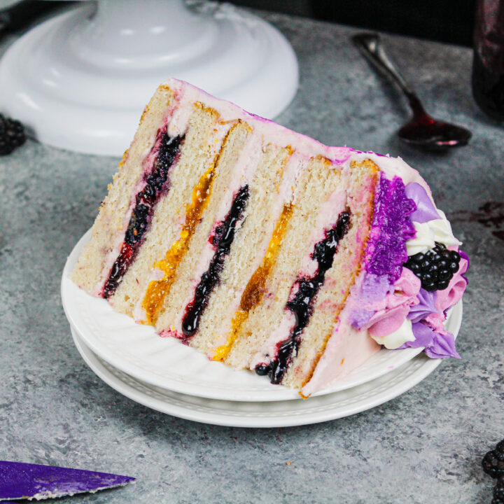 image of a slice of blackberry layer cake being assembled with cinnamon cake layers, blackberry jam, fresh blackberries, and blackberry peach buttercream