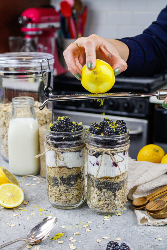 image of a lemon being zested into blackberry overnight oats