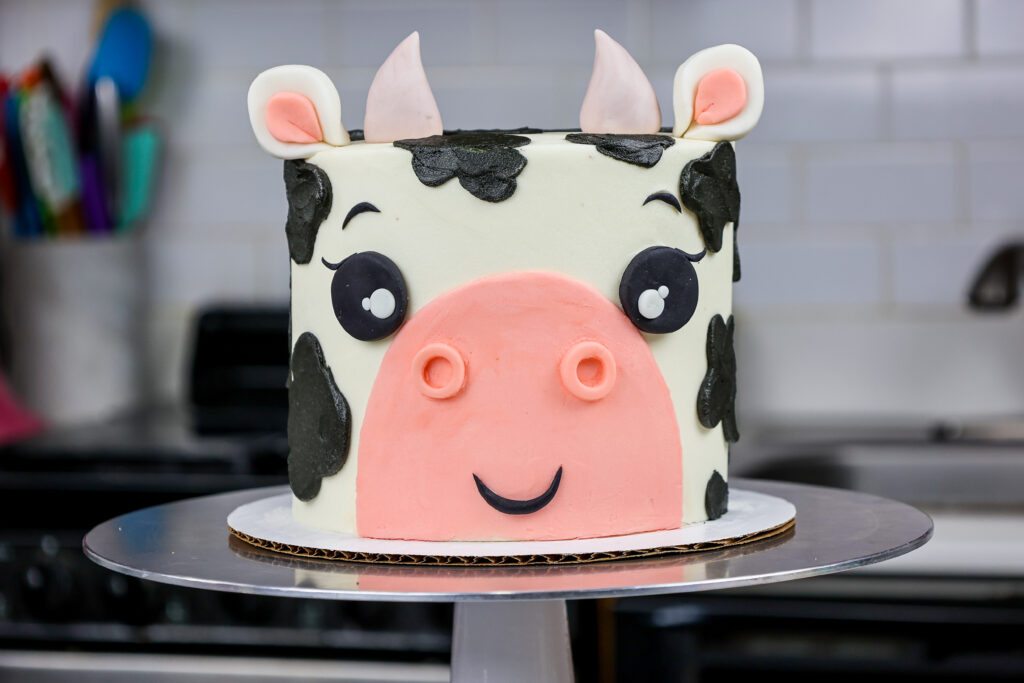 image of an adorable buttercream cow birthday cake made with marbled chocolate and vanilla cake layers