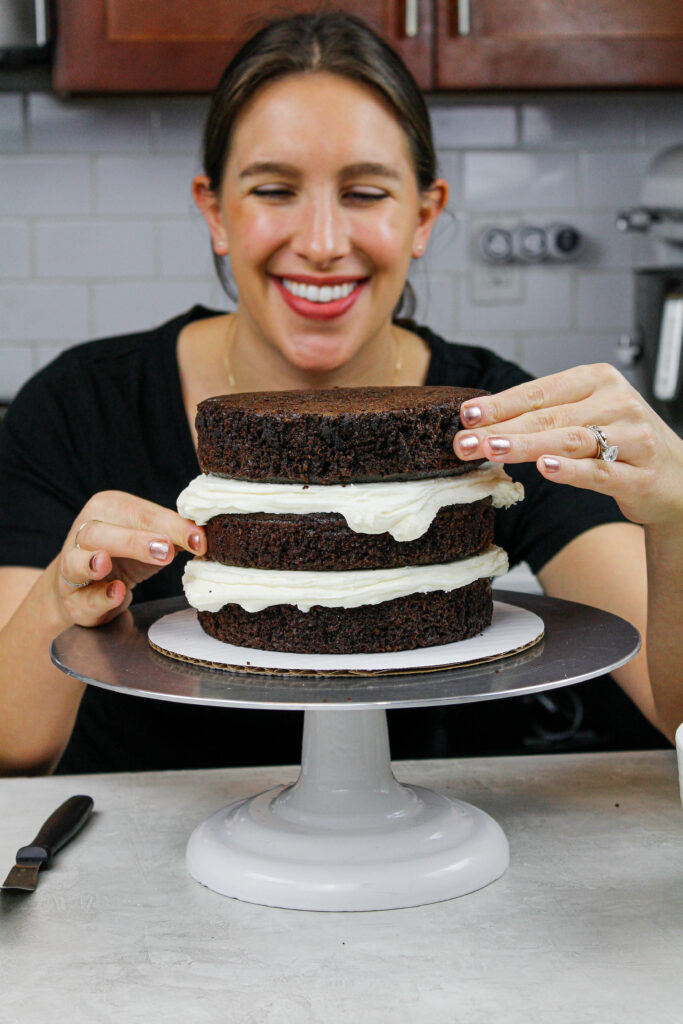 image of chocolate cake layers being stacked by chelsey white of chelsweets