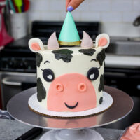 image of an adorable cow birthday cake made with marbled chocolate and vanilla cake layers and topped with a cute little party hat