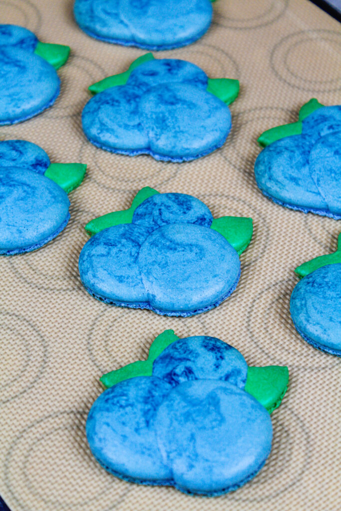 image of blueberry macaron shells that have been baked and have perfect little feet