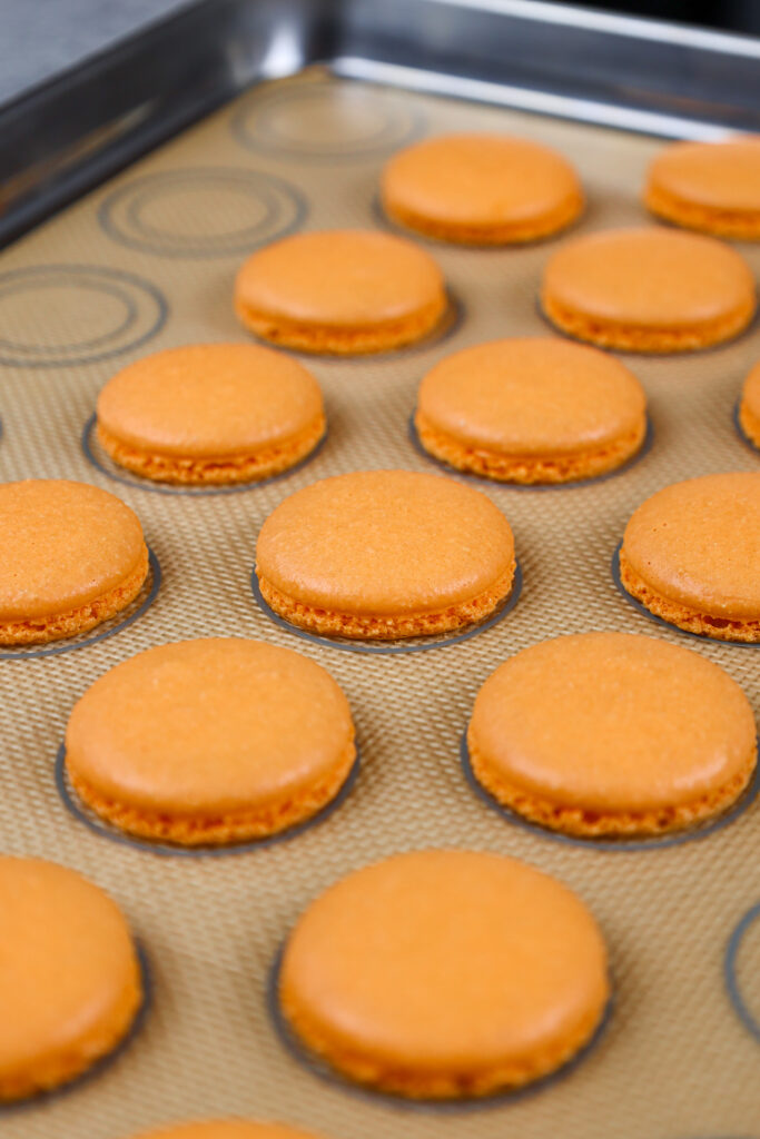 image of orange macaron shells that have been baked and have proper feet