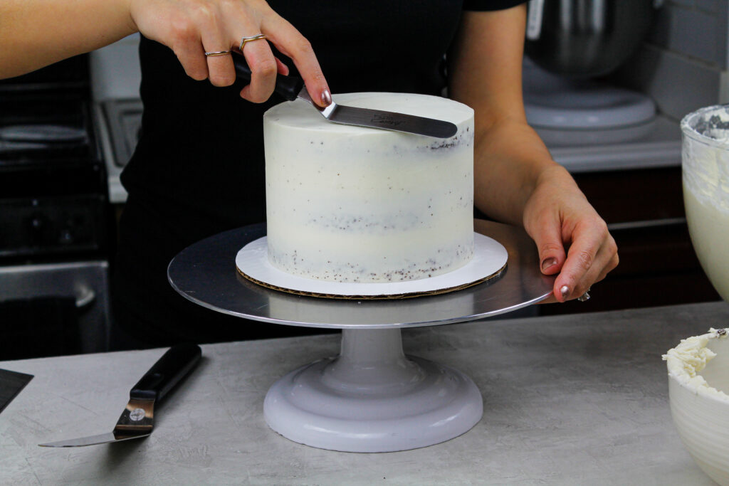 image of a chocolate being crumb coated with vanilla frosting to show How to Frost a Cake Smoothly
