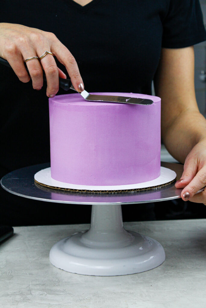 image of a buttercream cake being frosted with sharp edges and smooth sides to show How to Frost a Cake Smoothly