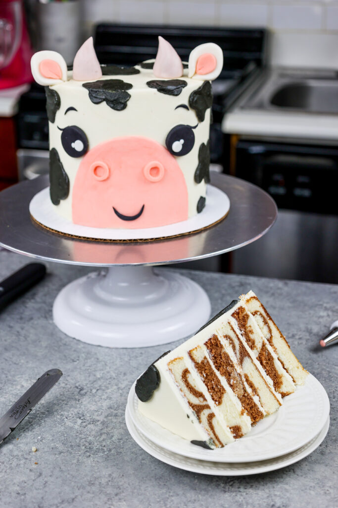 image of an adorable cow birthday cake made with marbled chocolate and vanilla cake layers