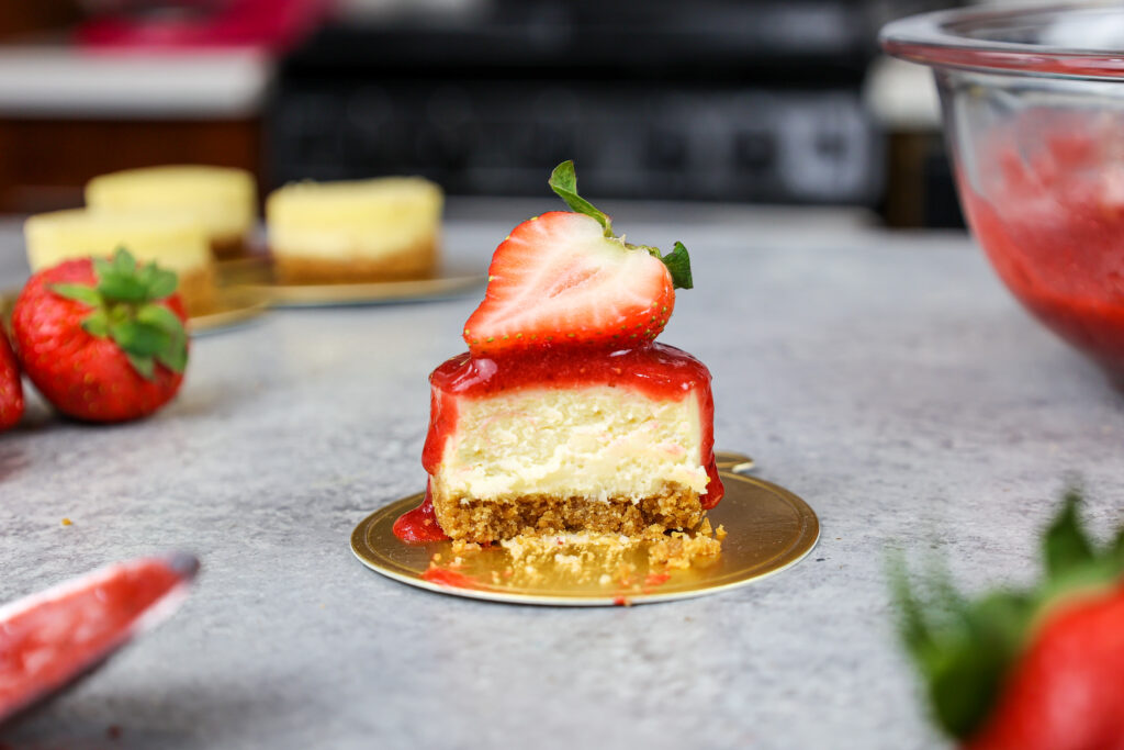 image of a mini strawberry cheesecake that's been cut into to show how creamy and fluffy it is