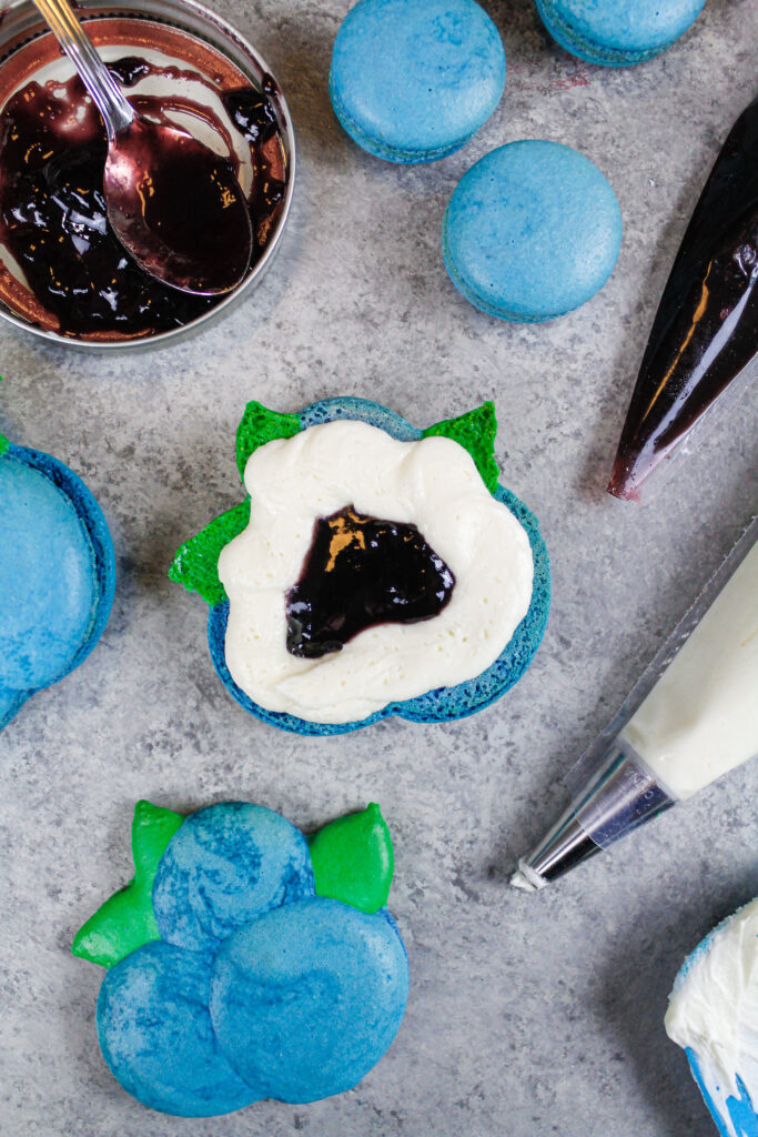 image of a blueberry macaron that's been filled with a ring of american buttercream and blueberry jam