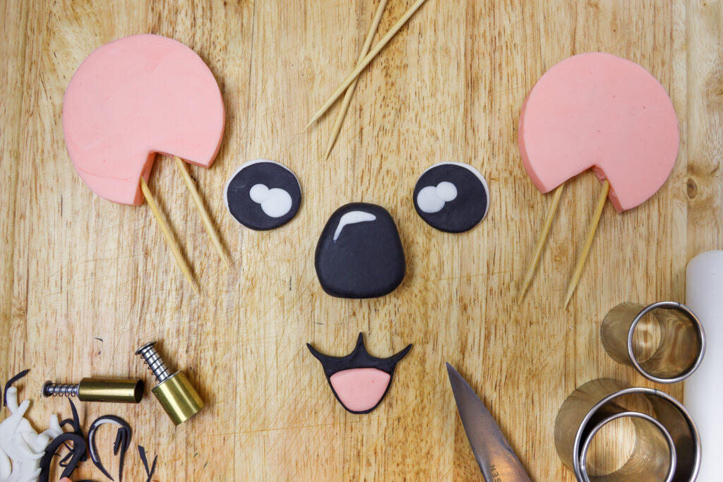 image of fondant cut outs shaped to make the face of a koala cake