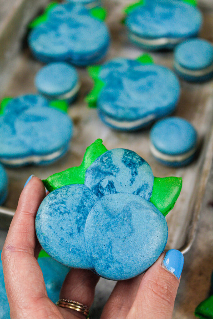 image of an adorable blueberry macaron that's being held up to show it's shape