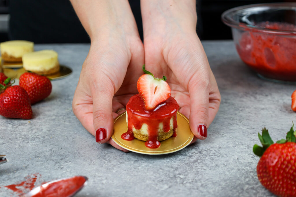 image of chelsey white of chelsweets holding a mini strawberry cheesecake in her hands
