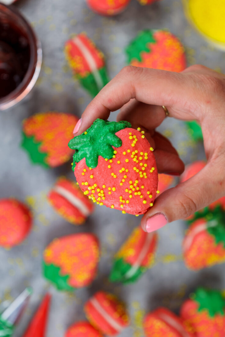 image of a strawberry shaped french macaron held up to show it's adorable shape