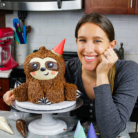 image of chelsey white, the baking blogger and content creator behind chelsweets with an adorable sloth birthday cake