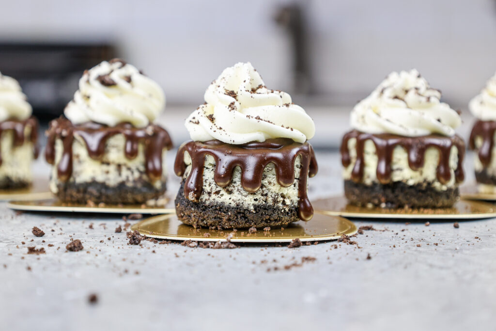 image of mini oreo cheesecakes lined up  and decorated with a chocolate ganache drip and whipped cream