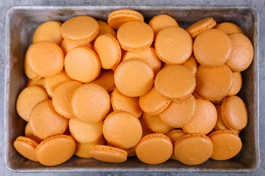 image of a tray of orange macaron shells that have been baked and cooled and are ready to be filled