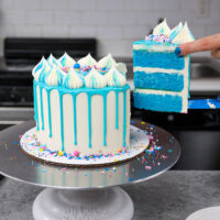 image of a blue drip cake being cut into to show its matching blue cake layers