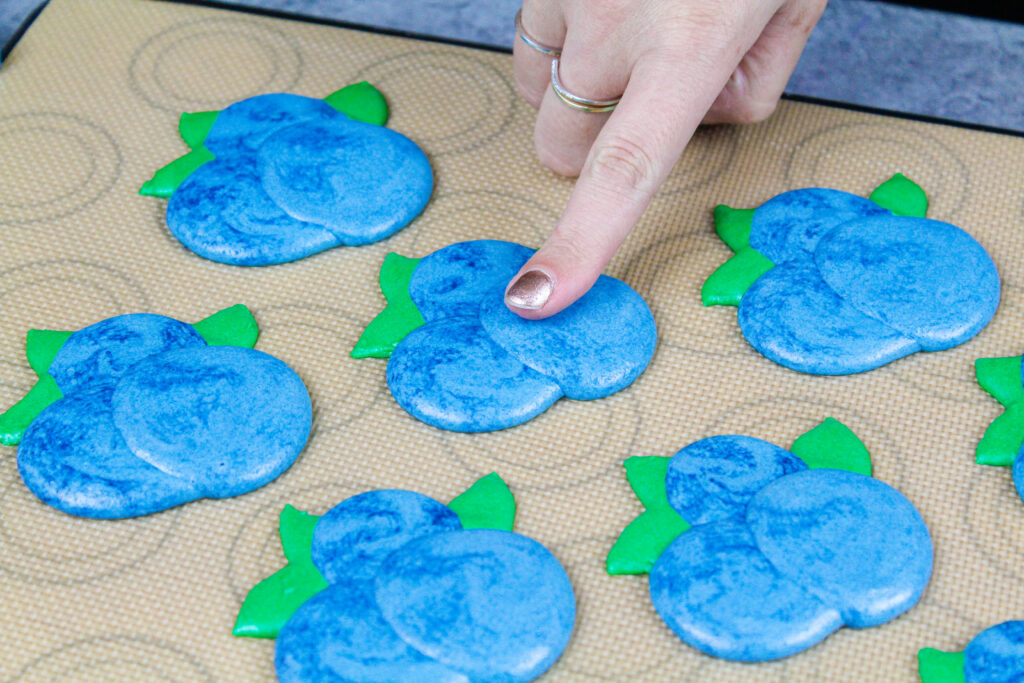 image of blueberry shaped macarons that have been piped and rested to form a skin before being baked