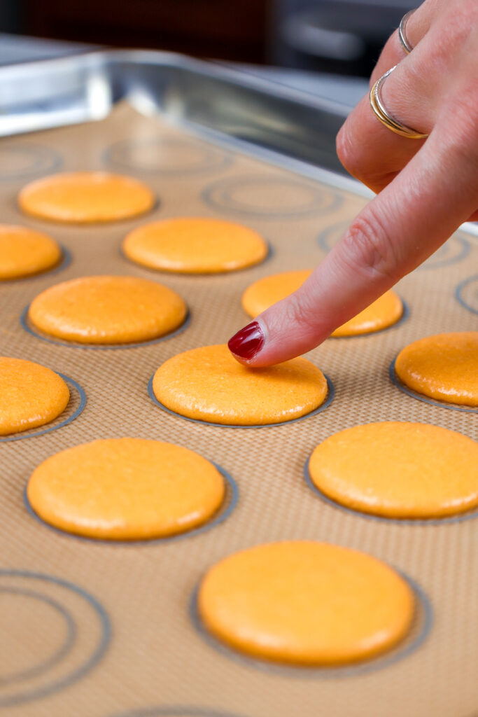 image of orange macaron shells that have rested and formed a skin before being baked