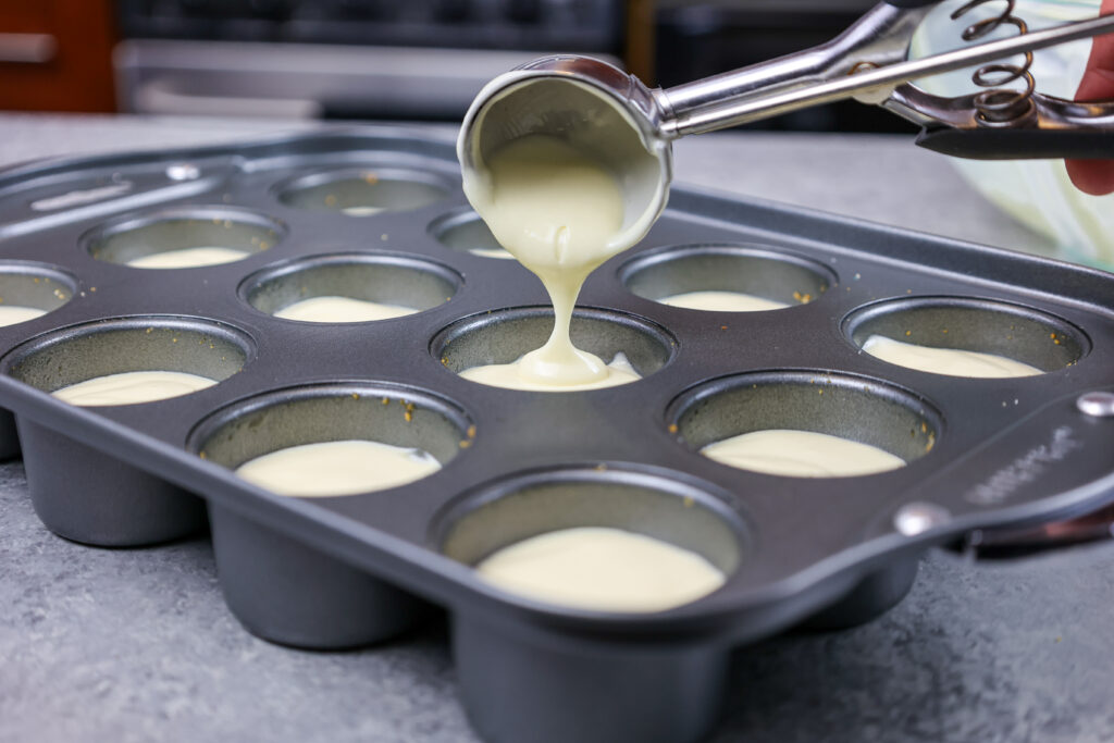 image of cheesecake batter being scooping into a pan to make mini strawberry cheesecakes