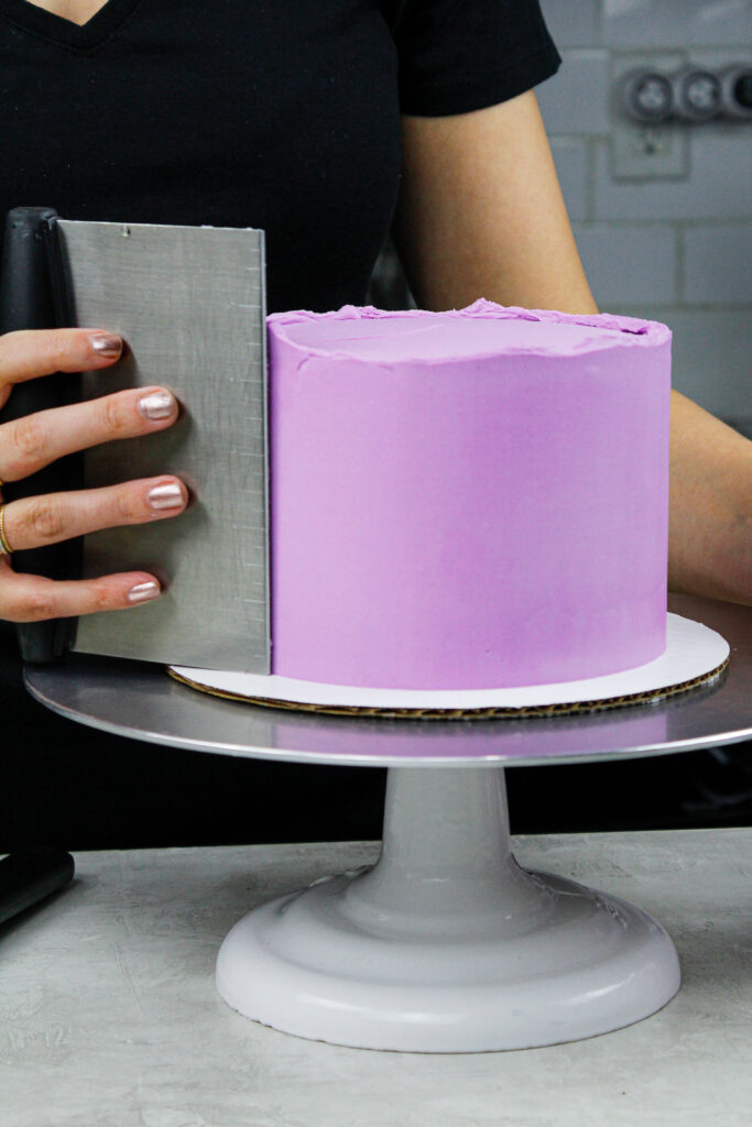 image of purple frosting being smoothed onto a cake with a bench scraper to show how to Frost a Cake Smoothly