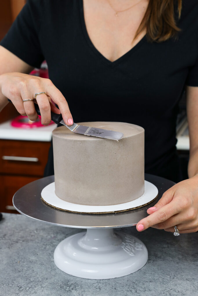image of grey buttercream being smoothed onto a 6-inch cake