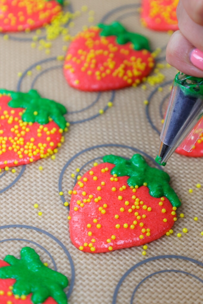 image of strawberry macaron shells being piped