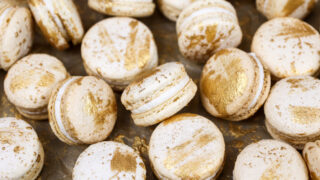 image of vanilla macarons made using the french method and decorated with edible gold paint