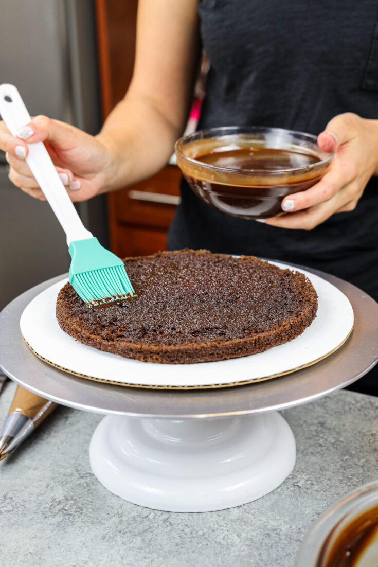 image of a chocolate cake layer being soaked with chocolate simple syrup