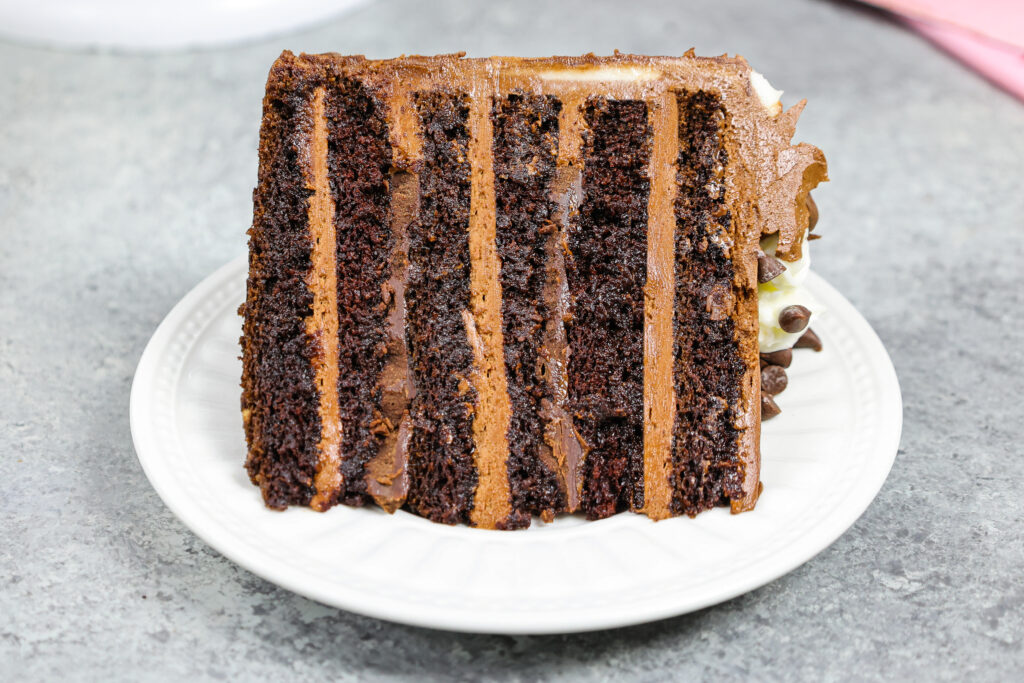 image of a triple chocolate cake slice that's filled with milk chocolate buttercream and dark chocolate ganache, and soaked with chocolate simple syrup