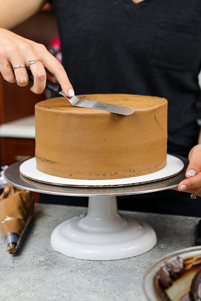 image of a triple chocolate cake being crumb coated before being decorated