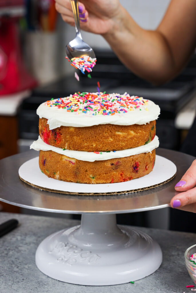 image of rainbow sprinkles being added between the cake layers of a gluten free funfetti cake