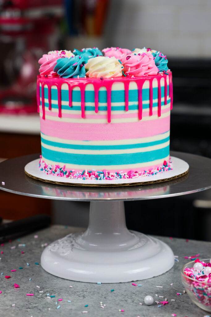 image of a gluten free funfetti cake that's been decorating with buttercream stripes and a pink drip