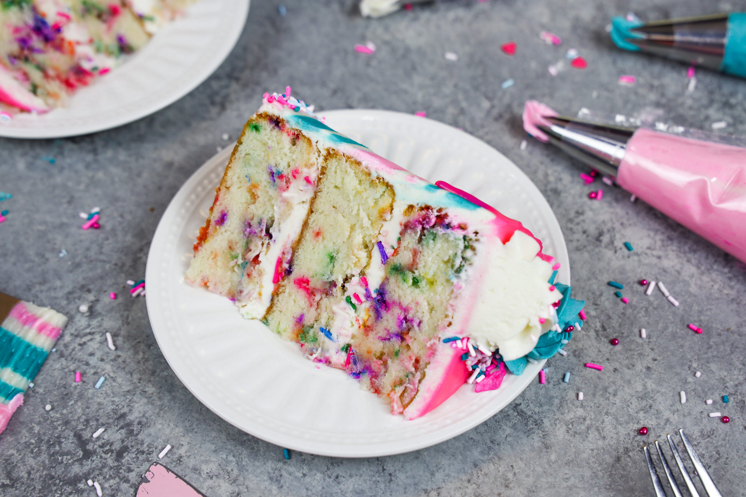 image of a slice of gluten free funfetti cake on a plate ready to be eaten