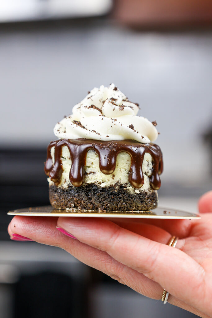 image of a mini oreo cheesecake held in the air to show how small it is
