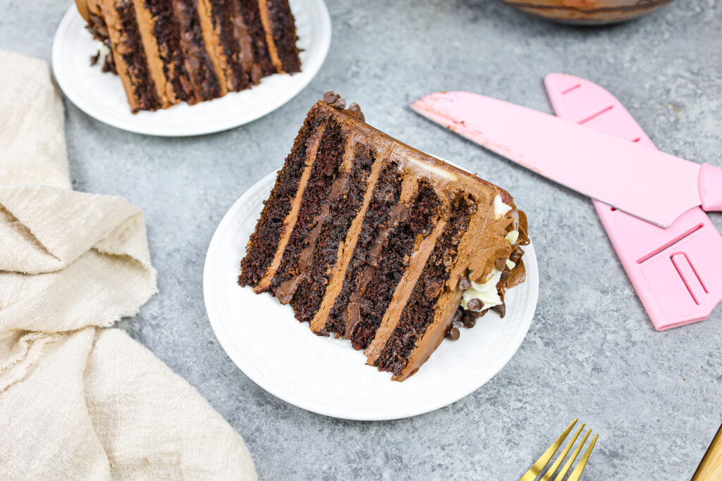 image of a triple chocolate cake slice that's filled with milk chocolate buttercream and dark chocolate ganache