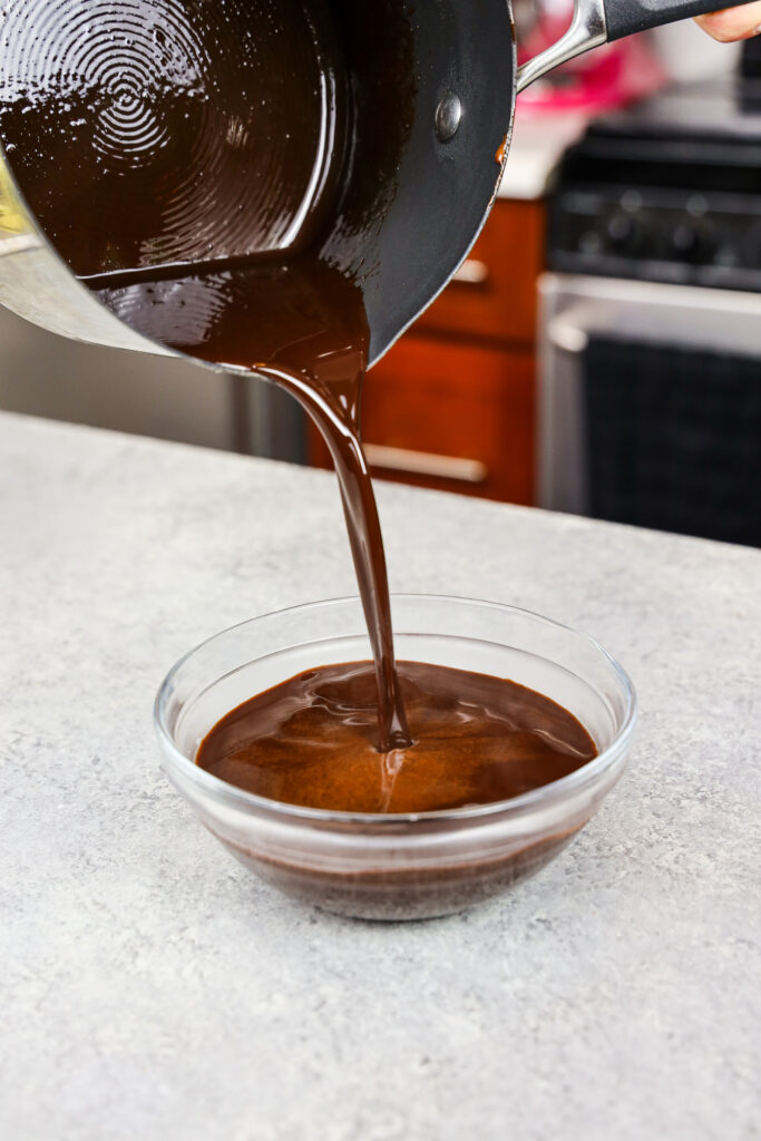 image of chocolate simple syrup being poured into a small bowl to cool