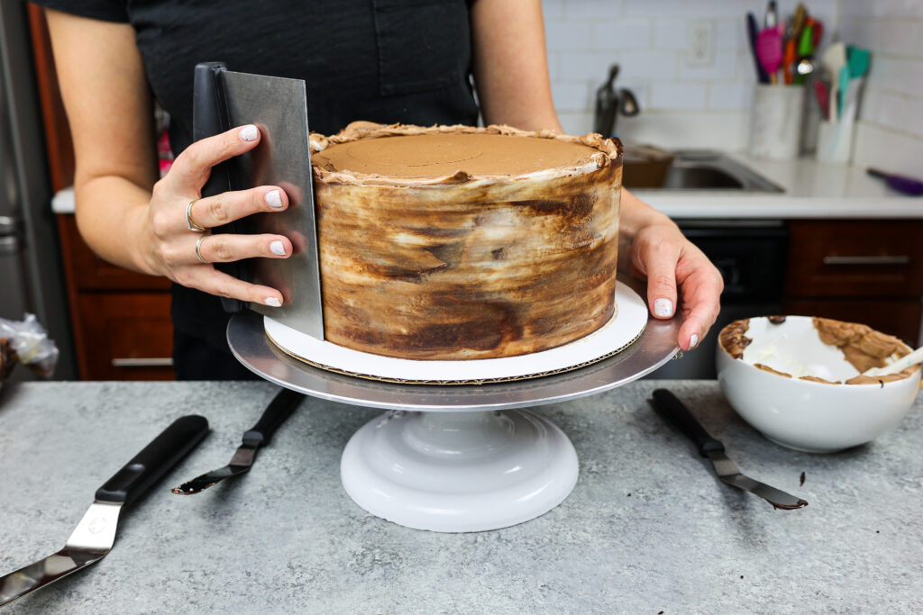 image of marbled chocolate buttercream being smoothed onto a triple chocolate cake