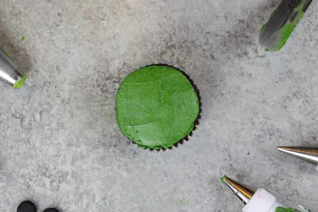 image of a frog cupcake being frosted and decorated with buttercream frosting