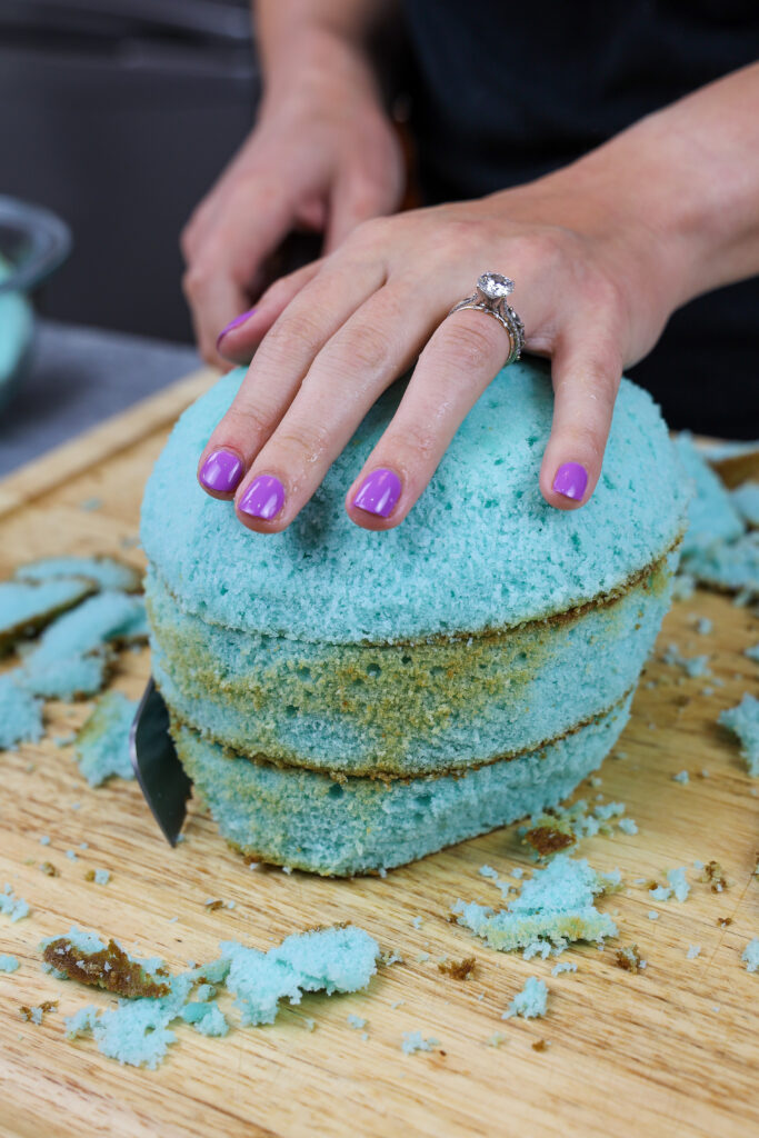 image of blue cake layers being trimmed to make a narwhal cake