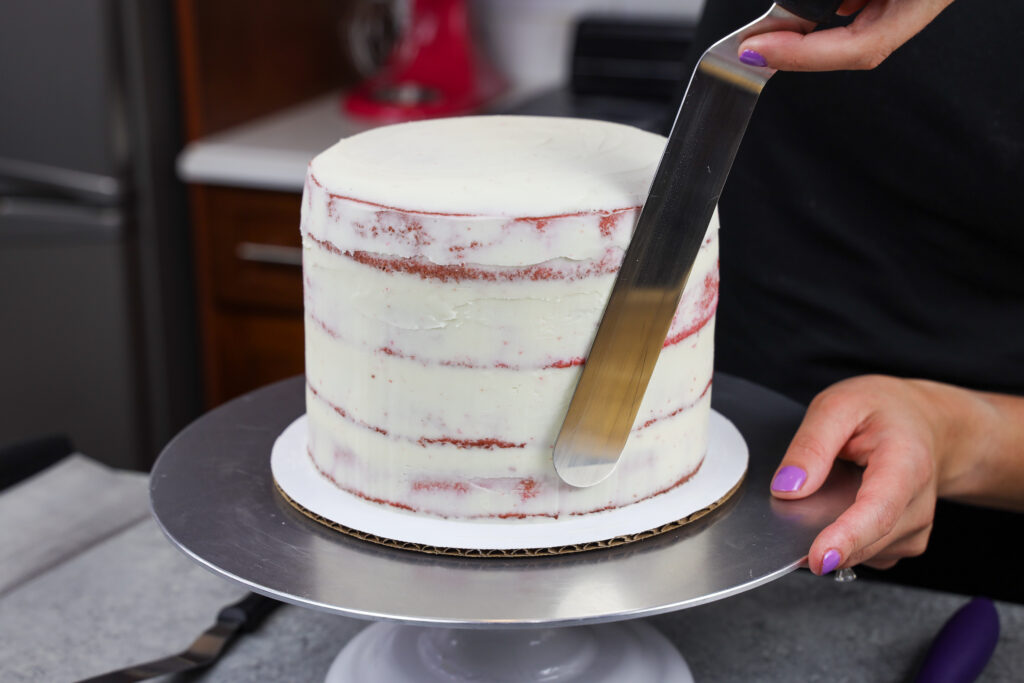 image of purple cake layers being stacked and crumb coated